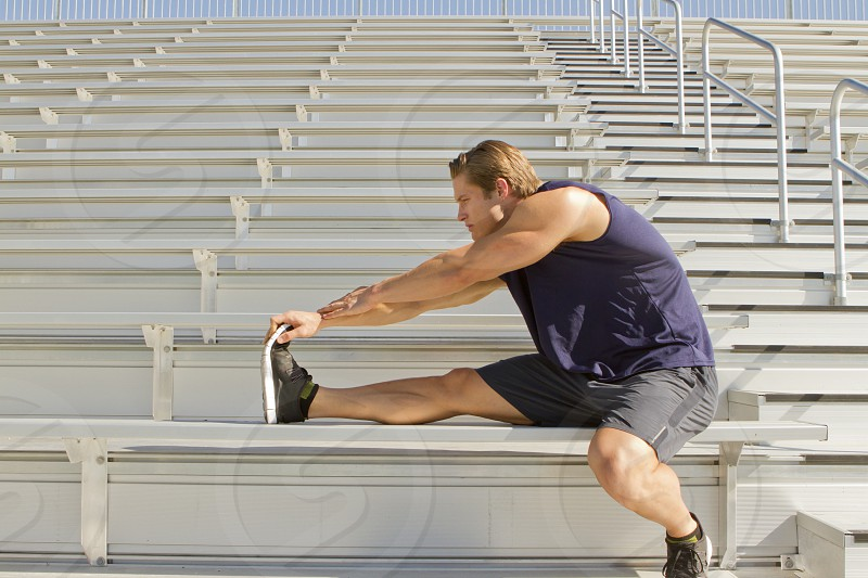 man in navy tank top and gray shorts and black athletic shoes stretching on bleachers photo