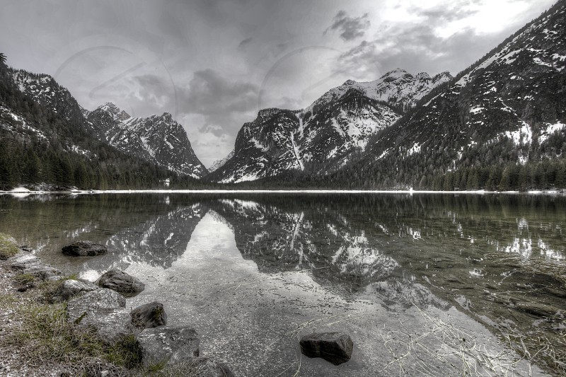 snow covered mountain beside clear lake water in grayscale photography photo