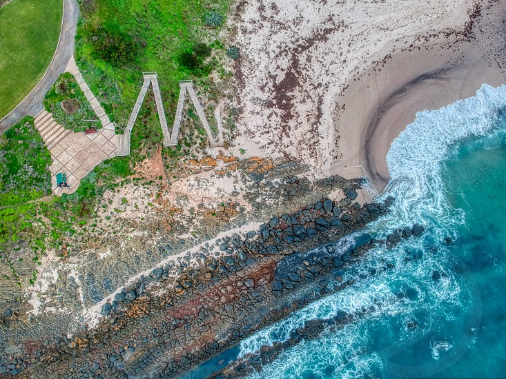 Drone image of the juxtaposition of beach rocks stairs and water photo