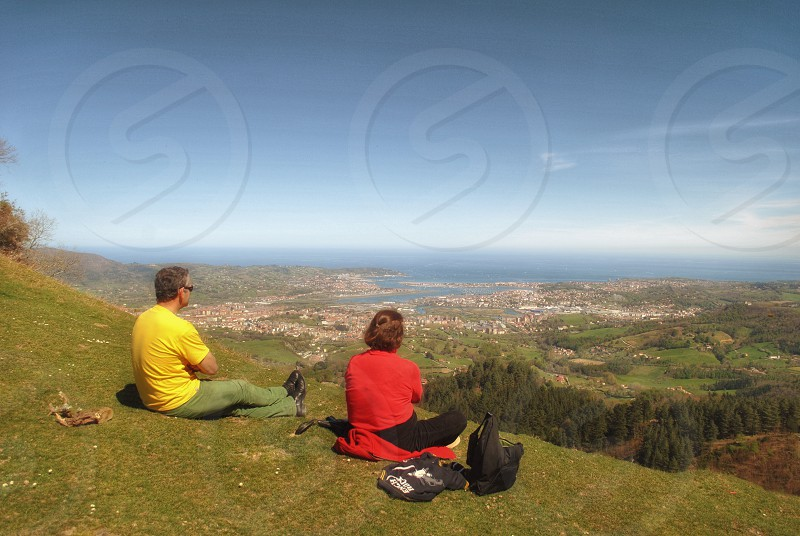 couple sitting on green grass covered hill top facing valley below photo