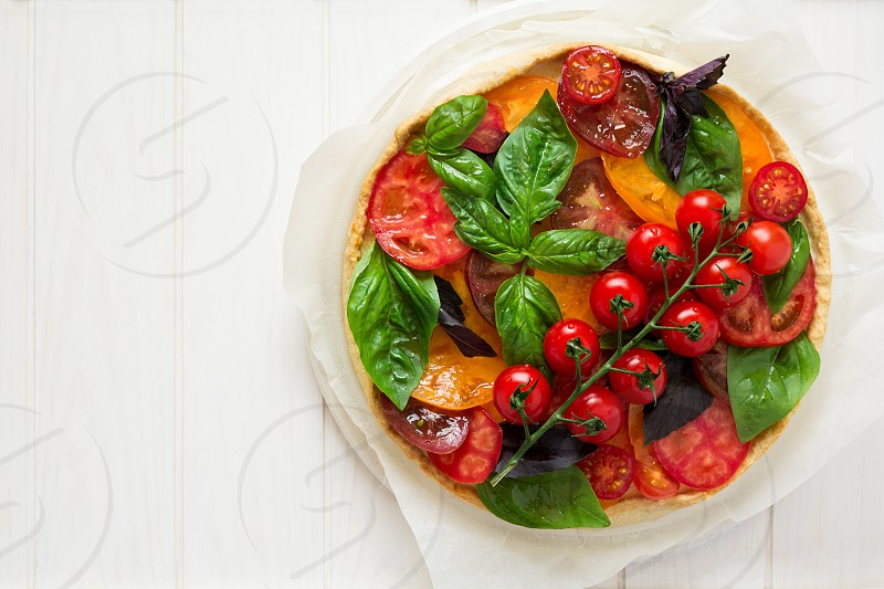Homemade tart with rikotta raw tomatoes and basil on white wooden background photo