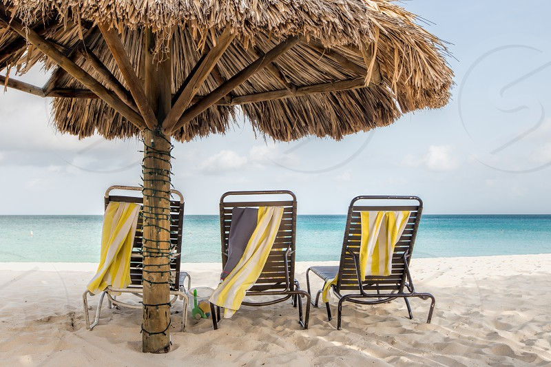 Beach chairs under a tikki umbrella on the beach in Aruba photo