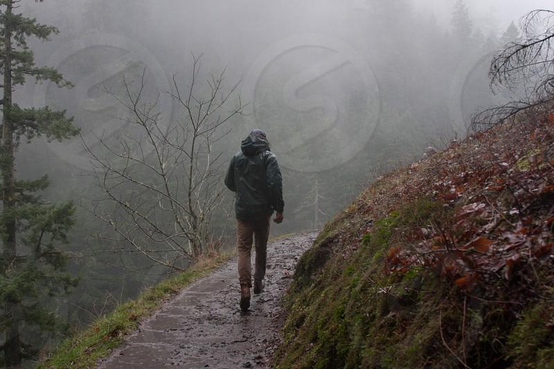 man in grey hoodie walking photo