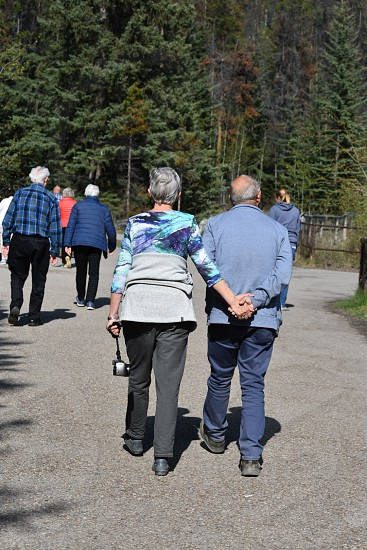 An elderly couple discreetly share their love holding hands while walking amidst a group of people photo