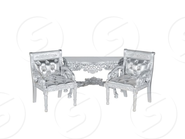 two silver leather  upholstery chairs with silver table on middle photo