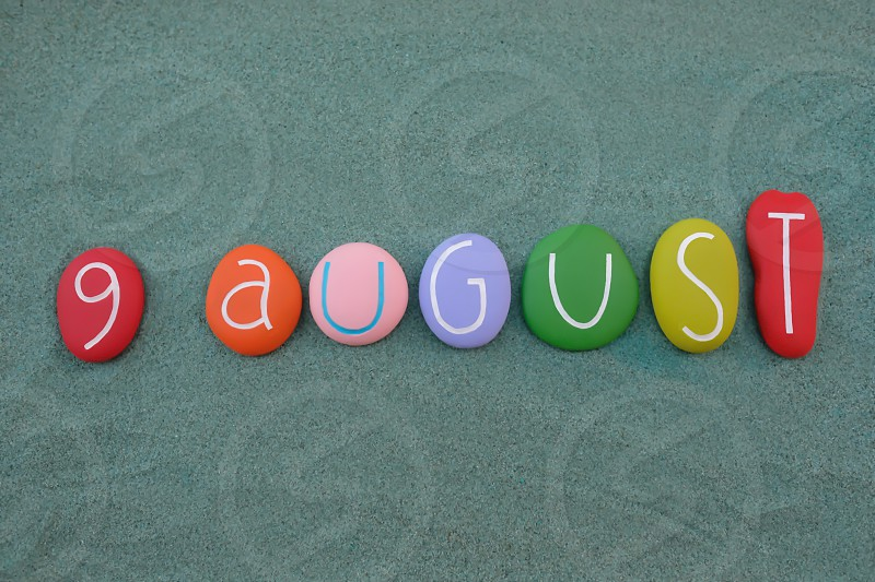 9 August calendar date composed with multi colored stones design over green sand photo