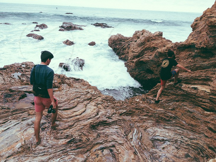 man and woman on a rock cliff seashore photo