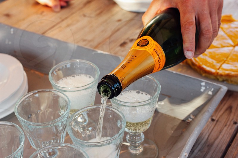 person pouring champagne on champagne glass photo