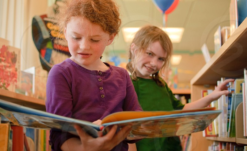 smiling girl in green shirt standing behind girl in purple henley shirt holding open book photo