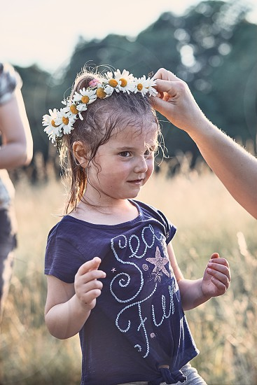 Mother putting a coronet of wild flowers on a head of little girl. Family spending time together on a meadow close to nature. Parents and children playing together. Candid people real moments authentic situations photo