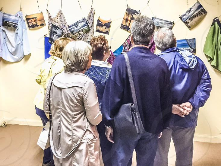 5 people standing looking at pictures hanged on wall photo