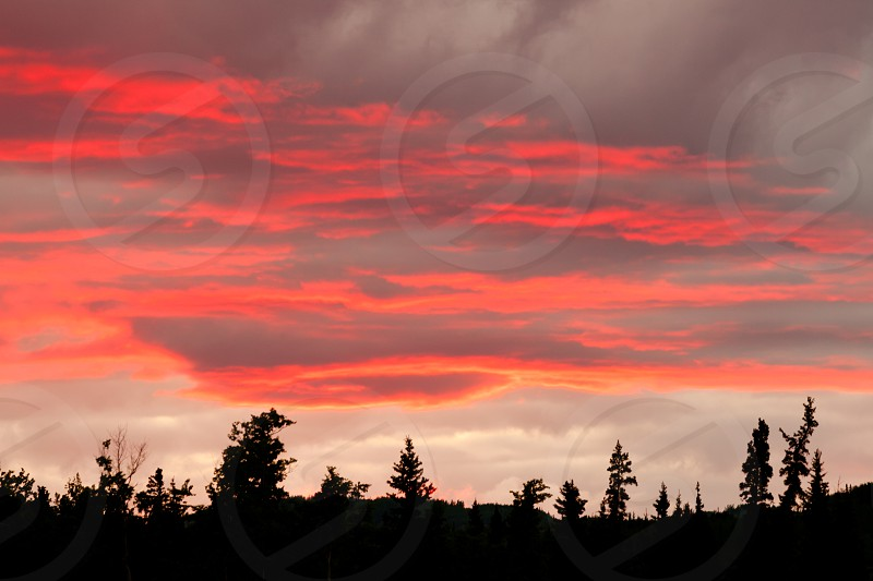 Cloudy sunset sky on fire over silhouette of forested hills Yukon Territory Canada photo
