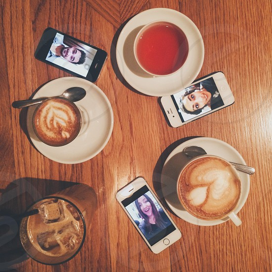 cups of coffee and tea on wood table with smart phones photo