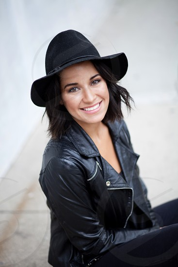 beautiful brunette girl in a black hat and leather moto jacket and a happy smile photo