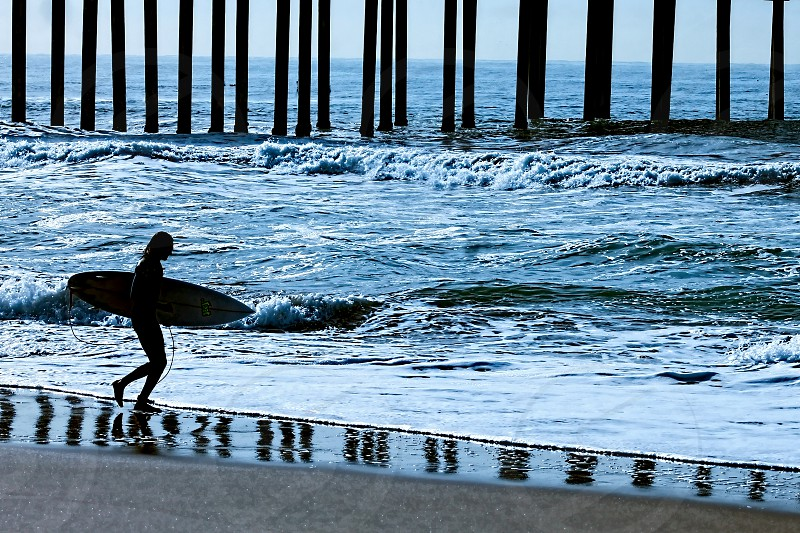 Silhouette of a female surfer holding a surfboard walking along the edge of the ocean near a reflection of a pier photo