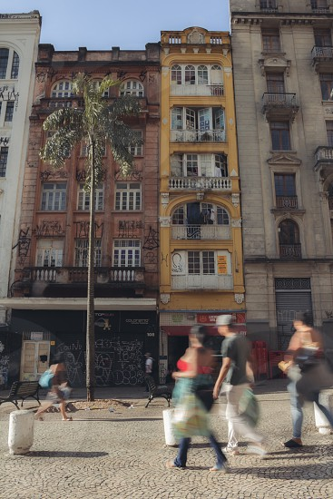 old antique movement motion people walking downtown building Brazil commerce bars simple poor photo