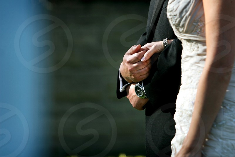 A Bride and Groom hold hands during their outdoor wedding ceremony.  He's wearing a black tux and wrist watch.  She's in a creamy white bridal gown with a diamond bracelet. photo