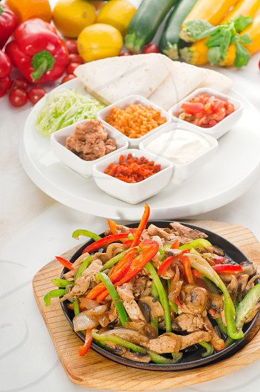 original fajita sizzling smoking hot served on iron plate and fresh vegetables on background MORE DELICIOUS FOOD ON PORTFOLIO photo