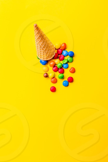 Ice creame cone with candy on yellow background. Minimalistic concept. photo