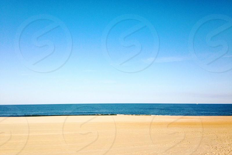 yellow sand beach under clear blue sky photo