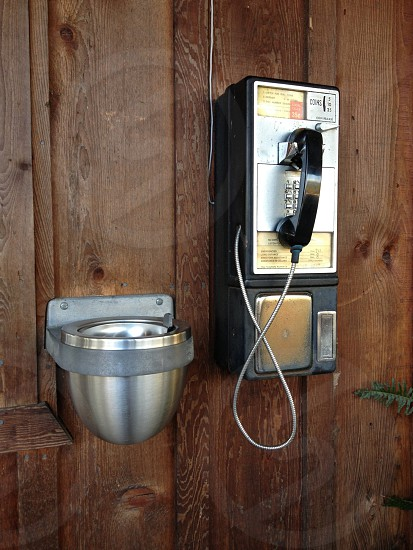 Old fashioned pay telephone and ashtray on wooden wall photo