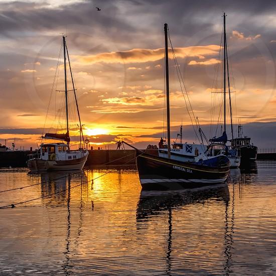 Dramatic sunset over small Scottish fishing harbor.  Boats. photo