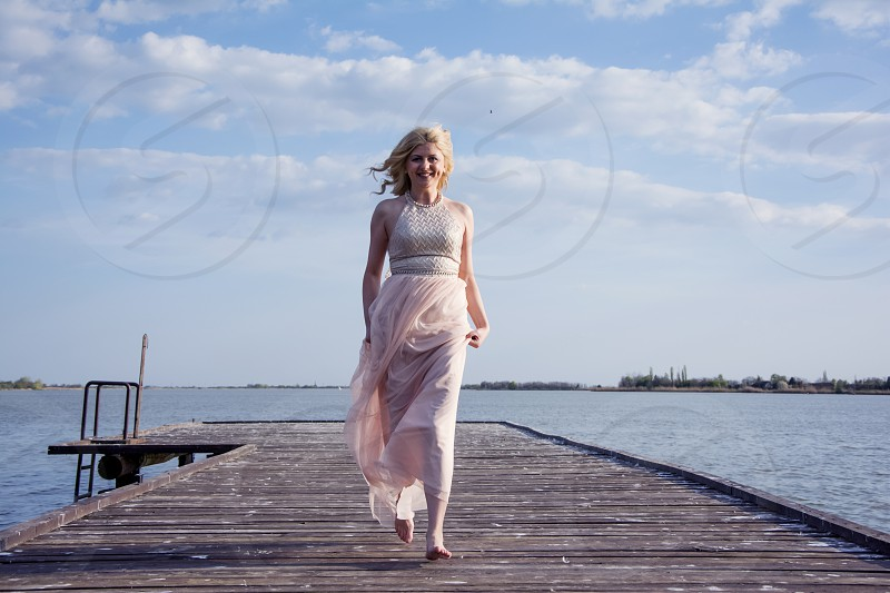 Blond woman running in evening gown on deck at lake feet above ground. photo
