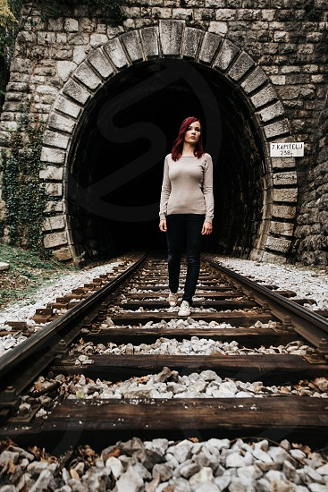 Young beautiful girl walking on a railroad in front of a tunnel. photo