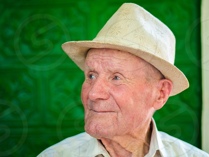 Very old man portrait with emotions. Grandfather happy and smiling. Portrait: aged elderly senior. Close-up of a pensive old man in white hat sitting alone outdoors at summer. photo