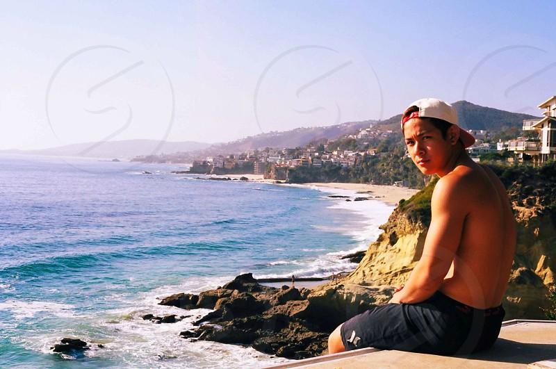 man sitting on ledge wearing a black hurley shorts photo