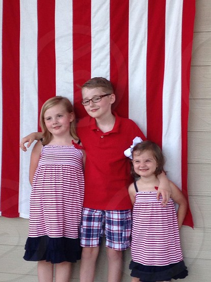 Patriotic children in front of flag on 4th of July. photo