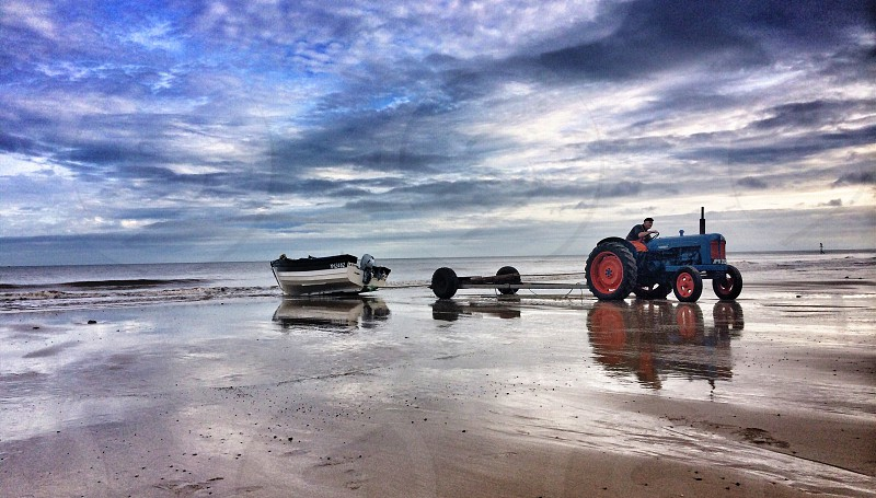 blue and orange tractor on beach photo