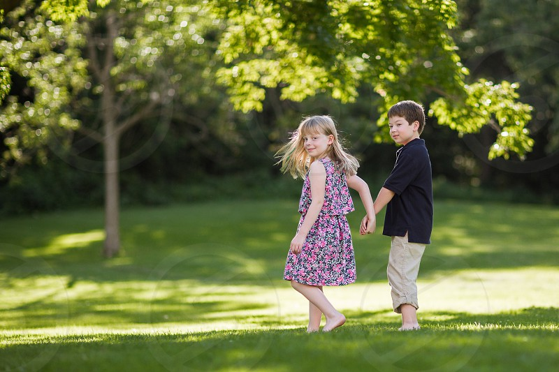 girl and boy holding hands standing on green grass during daytime photo