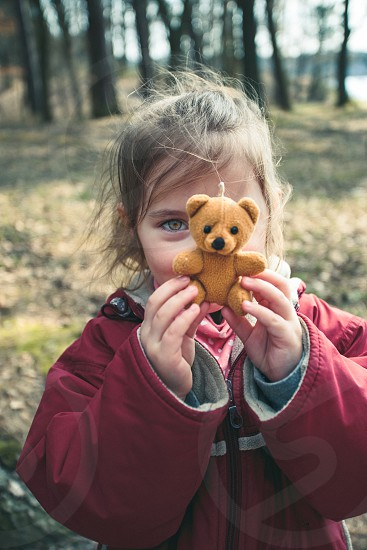 Little smilling happy girl playing with her little teddy bear toy in a park on sunny spring day. Child holding teddy at front of face looking at camera wearing red jacket photo