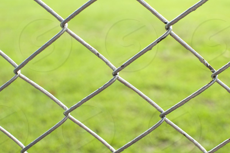 A metal fence with green background photo