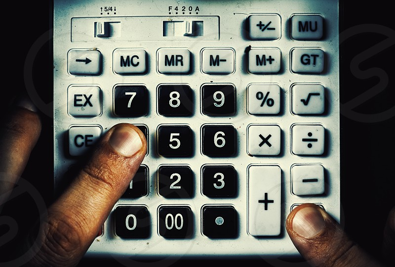 Conceptual composition about calculation two fingers on an old dusty calculator buttons.  photo