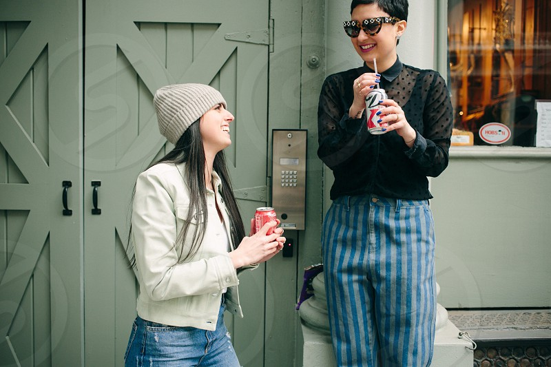 two women holding soda can laughing photo