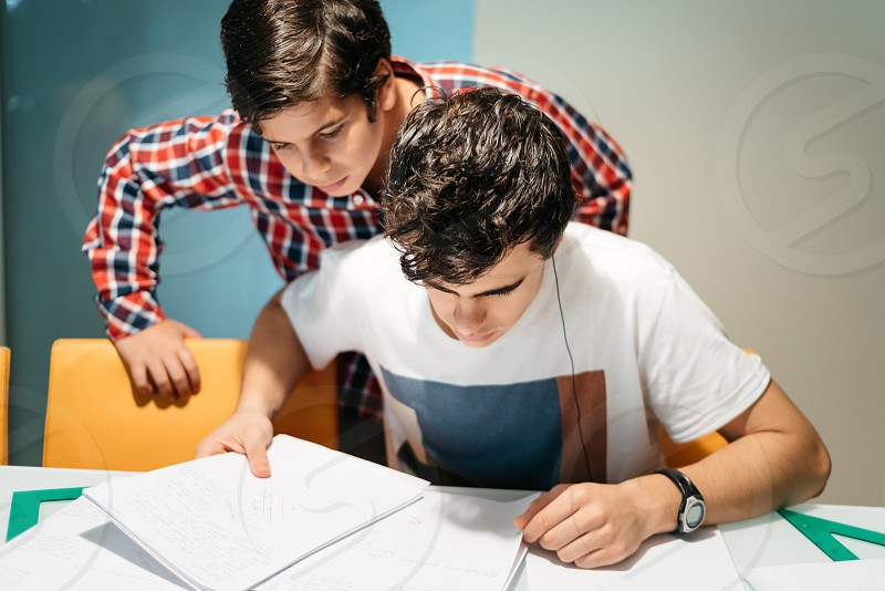 Boy helping young brother with homeworks photo