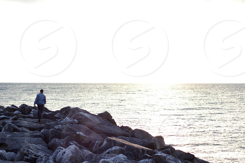 man on rock and sea photography photo