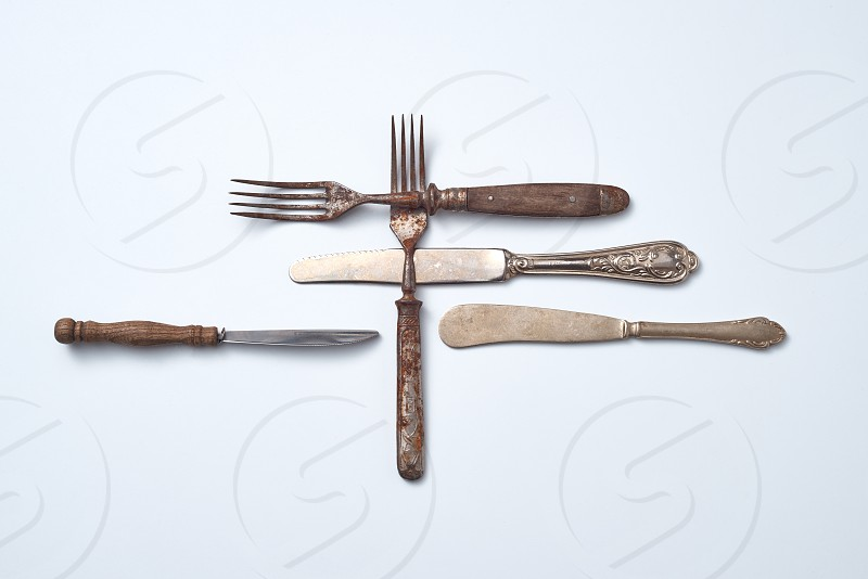 Metal knives with ornaments and forks with wooden handles on a gray background with space for text. Old vintage cutlery set. Flat lay photo