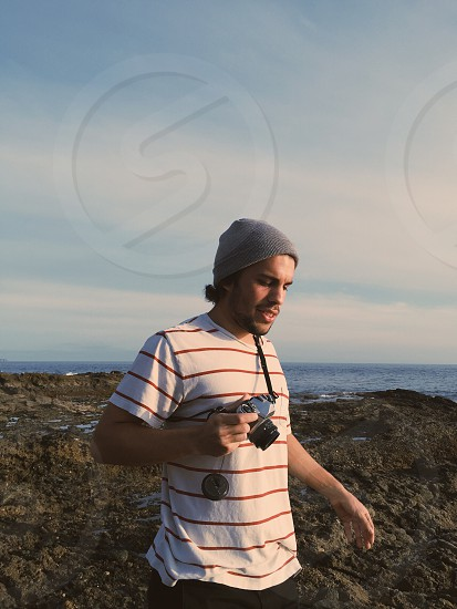 man in white and red striped crew neck t-shirt and grey knit cap in rocky beach holding camera photo