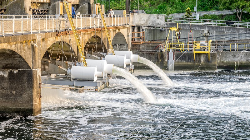 water flowing from white pipe with bridge during daytime photo