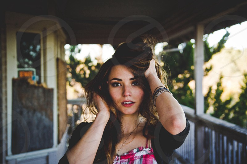 Woman with hands on her brown hair photo