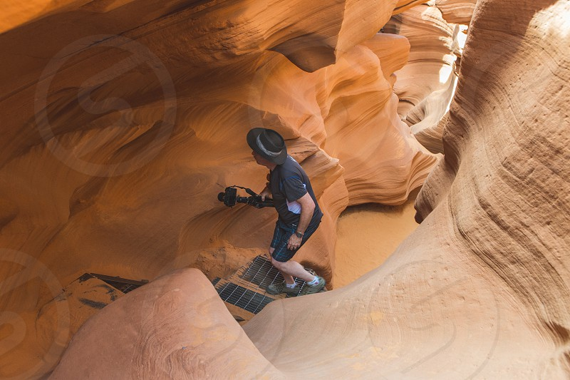 A man walks up a staircase in a slot canyon in Arizona.  photo