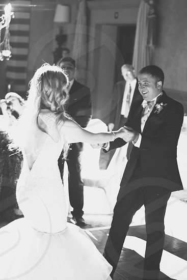 man in suit dancing with woman in dress in grayscale photo