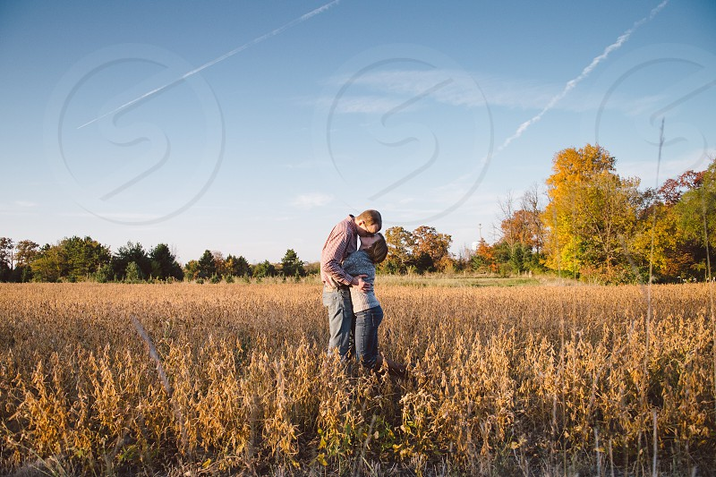man and woman kissing on brown field during daytime photo