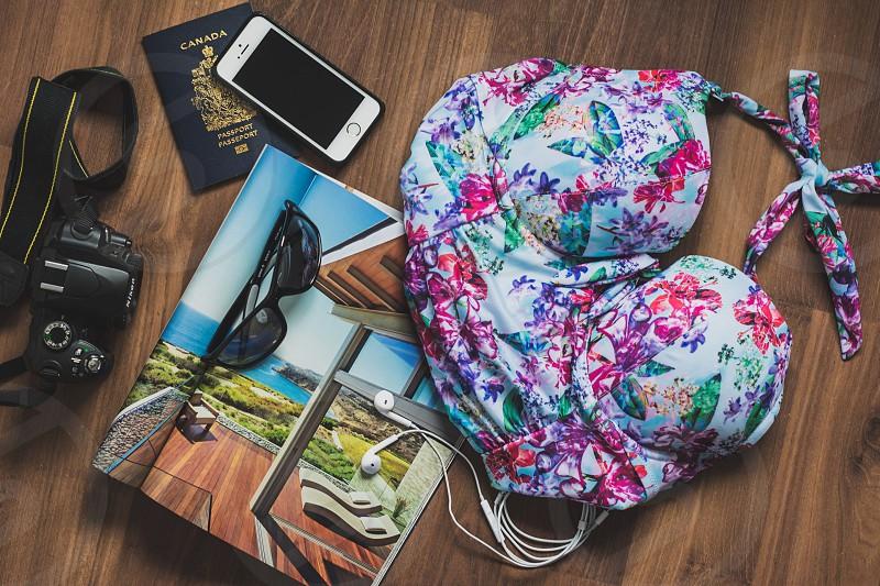 travel travel items travel flat lay vacation flat lay adventure experiences camera passport phone magazine sunglasses earbuds swimsuit  photo