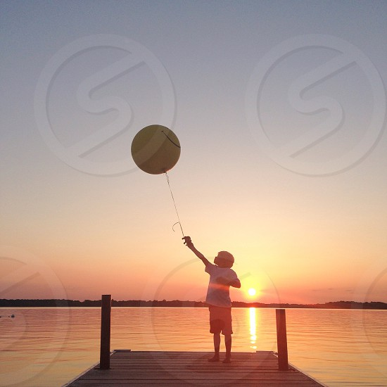 child with yellow balloon in front of orange sunset photo