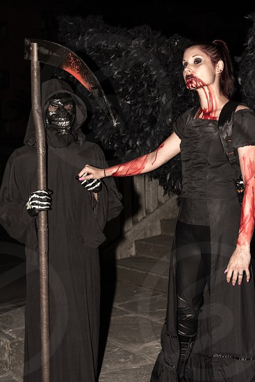 woman holding hand of person wearing grim reaper costume photo
