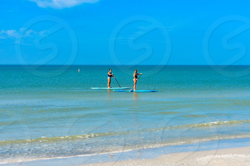 St. Pete Beach Florida. January 25 2019.  Couple enjoying stand up paddle board on blue sea background (3) photo